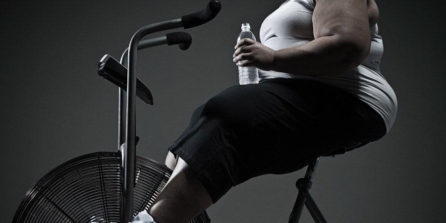 mujer con obesidad haciendo ejercicio en una bicicleta estática