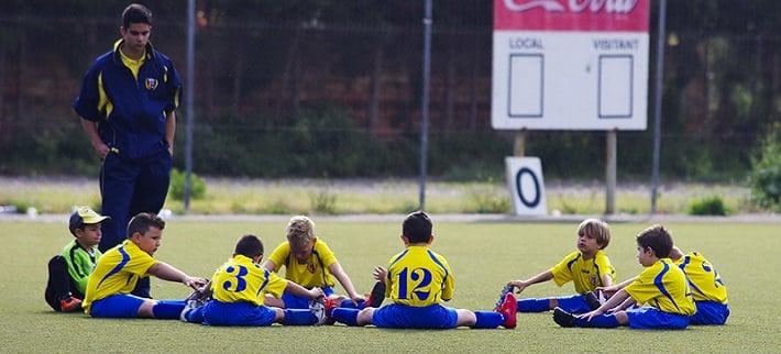 Futbolistas jóvenes estiran pre-competición