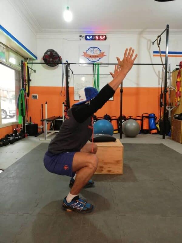 Sentadilla con manos arriba, ejercicio de dominancia de rodillas